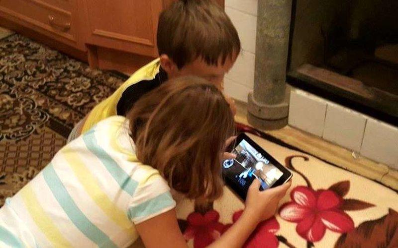 Дети играют в игру на планшете